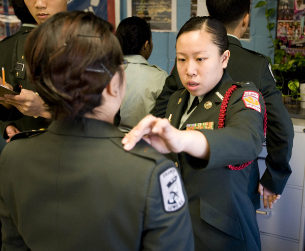 Alice Lam, part of the Patriot Battalion leadership, inspects a first-year Cadet's uniform. Cadets wear their uniforms and are inspected each Wednesday.